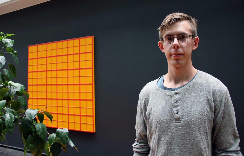 Man i ljusgrå tröja står mot en svart vägg. På vänstra sidan finns en gul geometrisk tavla och en grönväxt.
