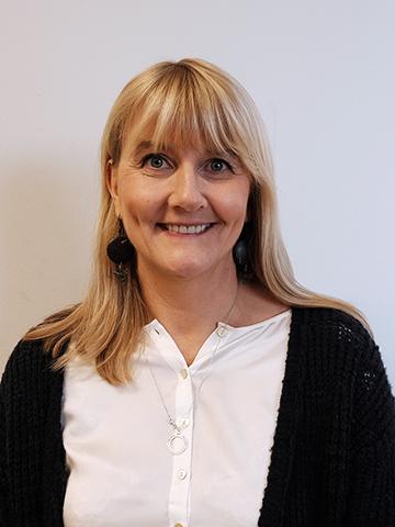 leende kvinna med långt blont hår i vit skjorta fotad mot en ljusgrå bakgrund