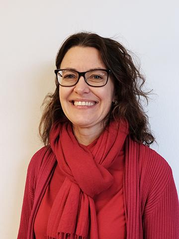 leende  kvinna i röd tröja och med svartbågade glasögon fotad mot en ljusgrå bakgrund